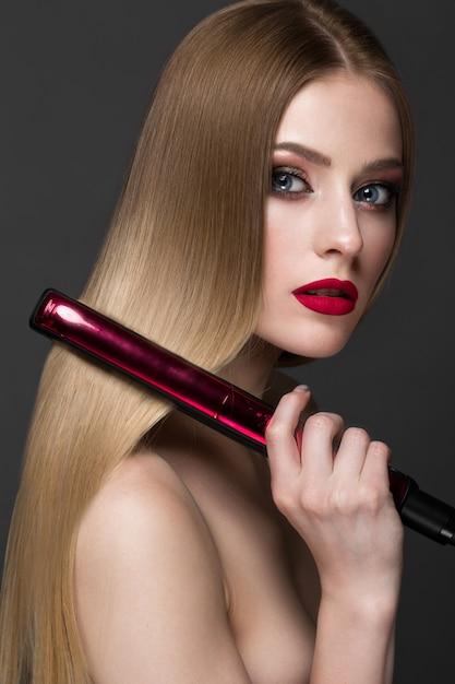 Mooi blond meisje met een perfect glad haar, krullen, klassieke make-up en rode lippen. mooi gezicht Premium Foto