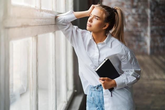 Mooi blond meisje met smartphone en notebook in haar handen. Premium Foto
