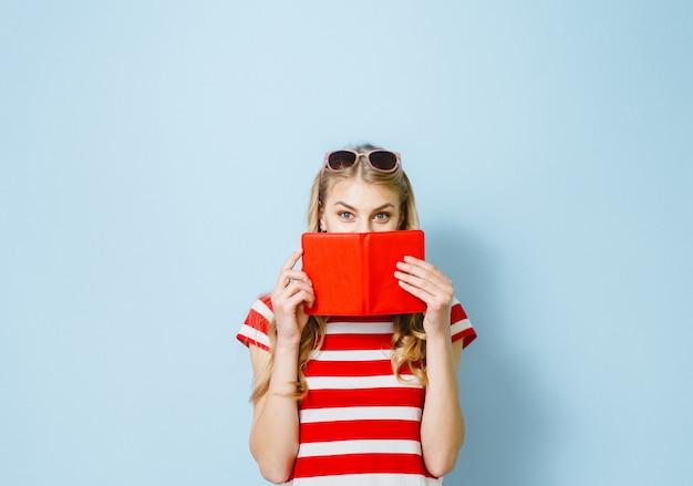 Mooi blond meisje verbergt haar ogen met een rode kaart tegen een blauwe achtergrond Premium Foto