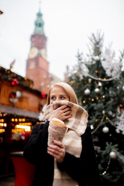 Mooi blonde met spitcake bij de kerstmismarkt in wroclaw, polen Premium Foto