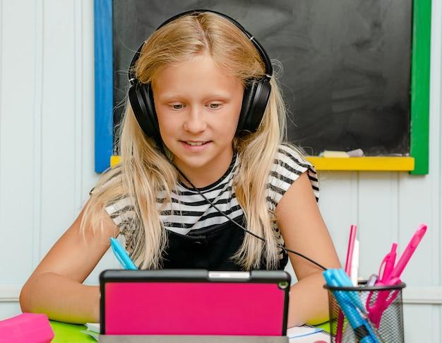 Mooi blondemeisje die online engelse cursus nemen. taal leren concept Premium Foto