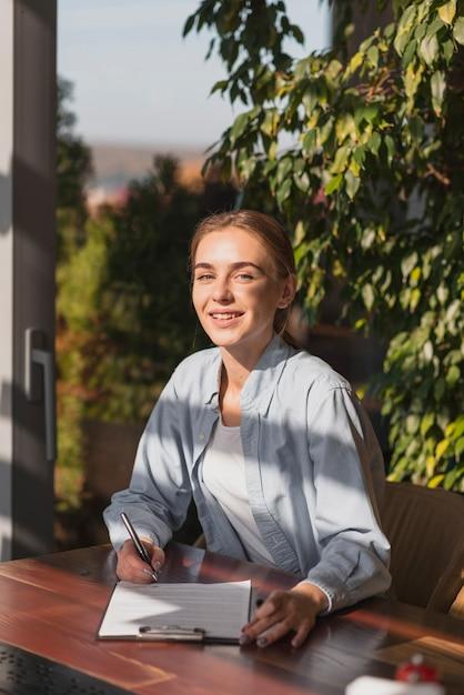 Mooi blondemeisje die op een klembord schrijven Gratis Foto