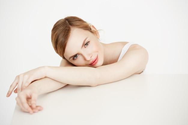 Mooi blondemeisje met perfecte schone huid het glimlachen zitting bij lijst. cosmetologie. gezichtsbehandeling. Gratis Foto