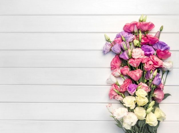 Mooi boeket van eustomabloemen op witte houten achtergrond. kopieer ruimte, bovenaanzicht, Premium Foto