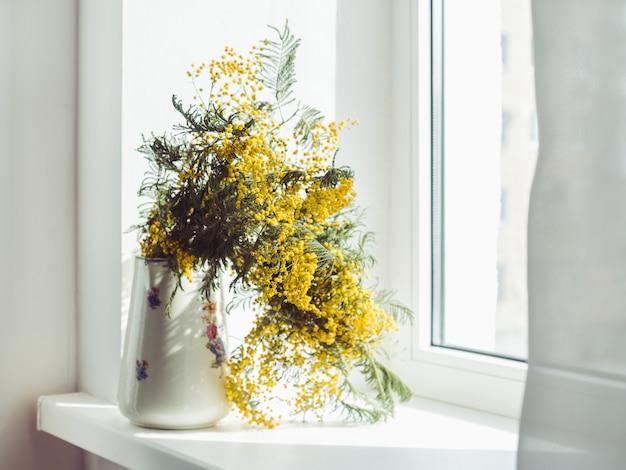 Mooi boeket van mimosa's in een vintage vaas Premium Foto