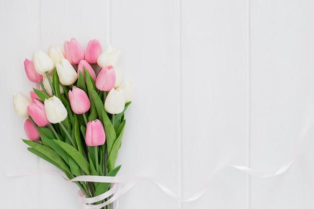 Mooi boeket van roze en witte tulpen op witte houten achtergrond Gratis Foto