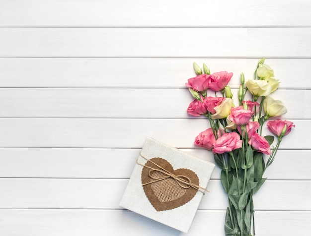 Mooi boeket van roze, paarse, gele eustomabloemen en handgemaakte geschenkdoos op witte houten achtergrond. kopieer ruimte, bovenaanzicht Premium Foto