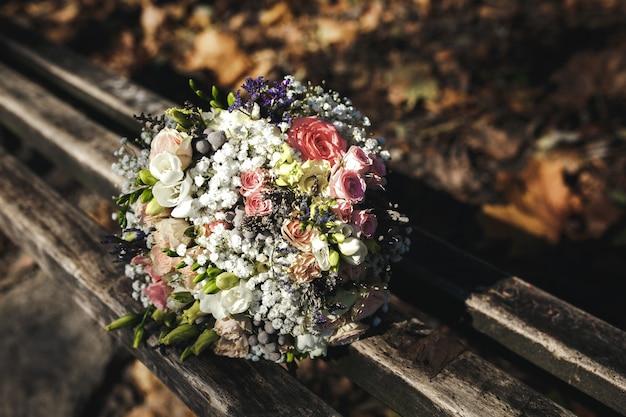 Mooi bruidsboeket liggend op een bankje in het park, herfst bruiloft Gratis Foto