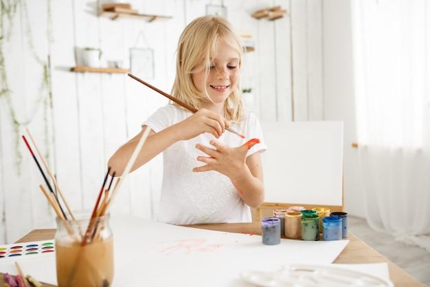 Mooi, creatief en druk blond meisje in wit t-shirt puttend uit haar handpalm met een borstel. Gratis Foto