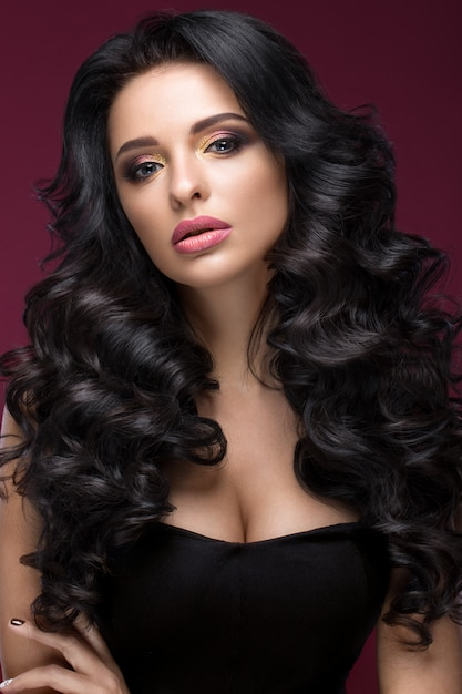 Mooi donkerbruin model: krullen, klassieke make-up, gouden sieraden en rode lippen. het schoonheidsgezicht. Premium Foto