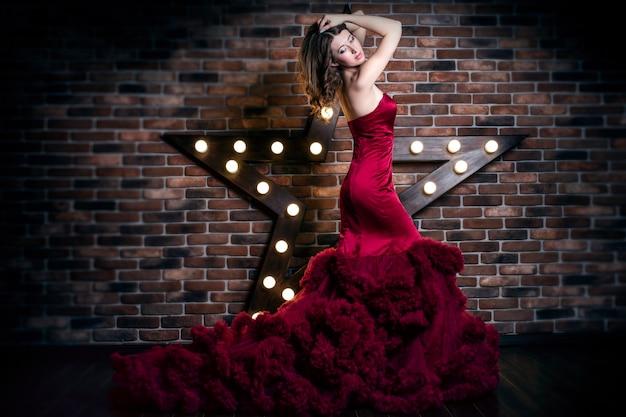 Mooi donkerbruin vrouwenmodel in luxe rode kleding met make-up Premium Foto