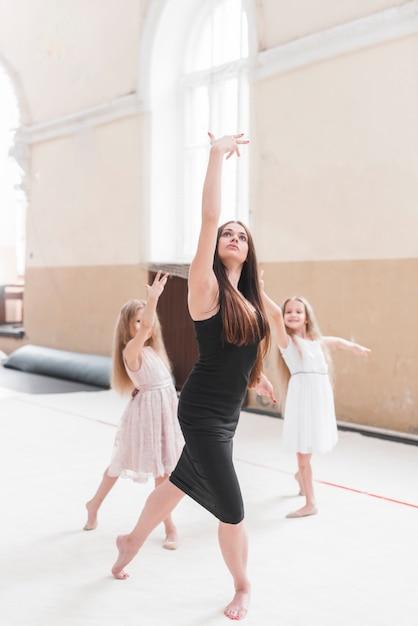 Mooi elegant wijfje dat met twee meisjes in dansstudio danst Gratis Foto