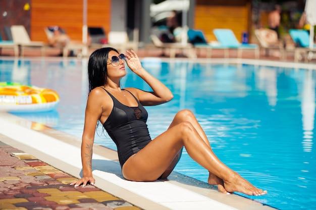 Mooi en sexy meisje in badmode die dichtbij zwembad ontspannen Premium Foto