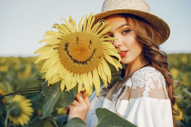Mooi en stijlvol meisje in een veld met zonnebloemen Gratis Foto