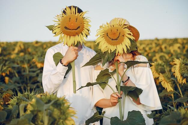 Mooi en stijlvol paar in een veld met zonnebloemen Gratis Foto