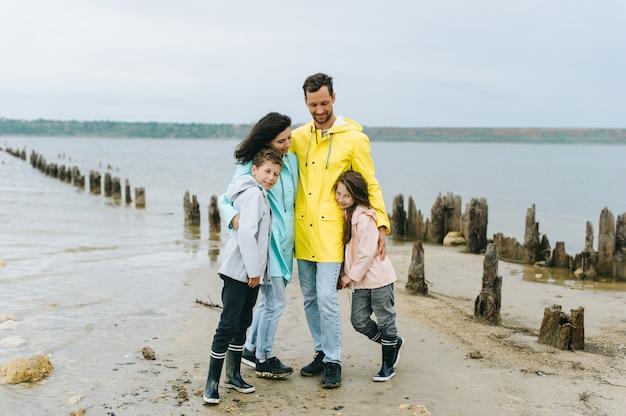Mooi familieportret gekleed in kleurrijke regenjas dichtbij het meer Premium Foto