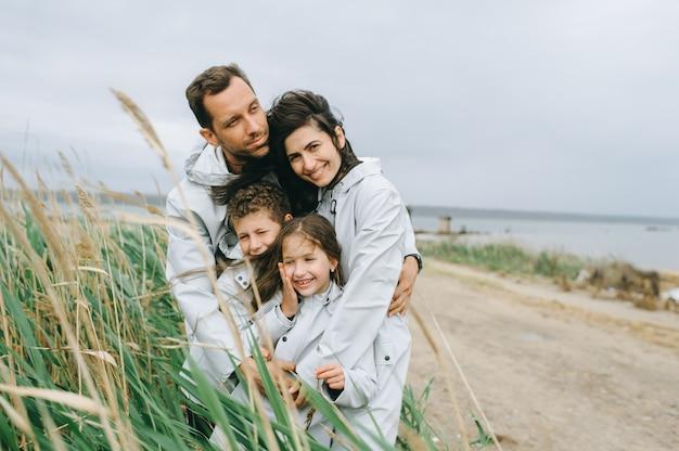 Mooi familieportret gekleed in regenjas dichtbij het meer Premium Foto
