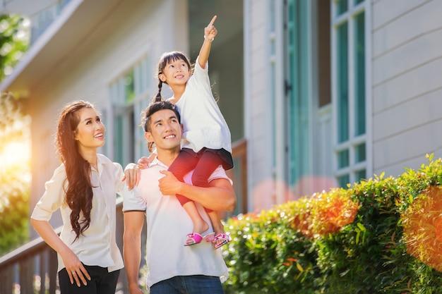 Mooi familieportret lachend buiten hun nieuwe huis Premium Foto