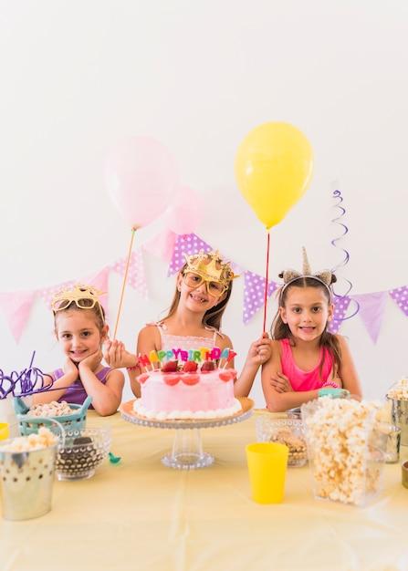 Mooi feestvarken met haar vrienden die oogmasker dragen die zich achter verscheidenheid van voedsel op lijst bevinden Gratis Foto