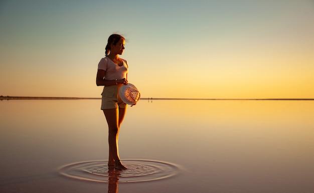 Mooi gelukkig jong meisje wandelen langs het spiegel roze zoutmeer genieten van de warme avondzon kijken naar de vurige zonsondergang en haar spiegelbeeld Premium Foto