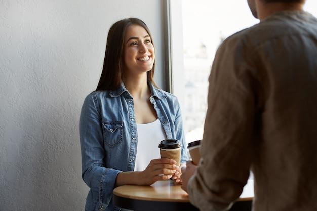 Mooi gelukkig meisje met donker haar in wit t-shirt onder denim shirt, drinkt koffie en lacht, luisterend naar het verhaal van vriend van gisteren feest. Gratis Foto