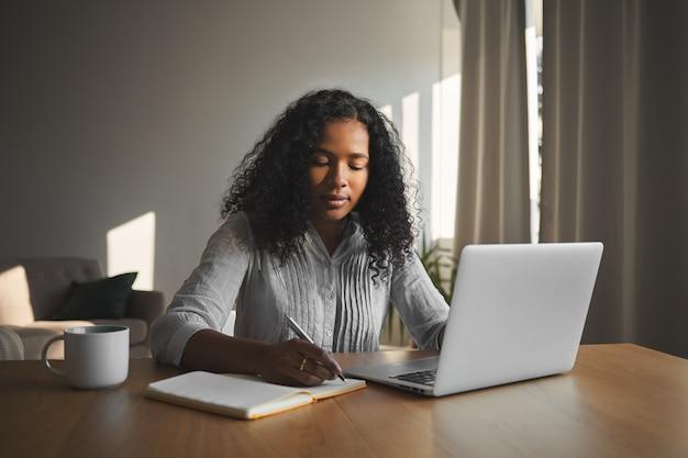 Mooi gemengd ras student meisje met omvangrijke kapsel thuis opdracht in haar kamer werken, zittend aan een houten bureau, laptop gebruikt en opschrijven in beurt. mensen, technologie en onderwijs Gratis Foto