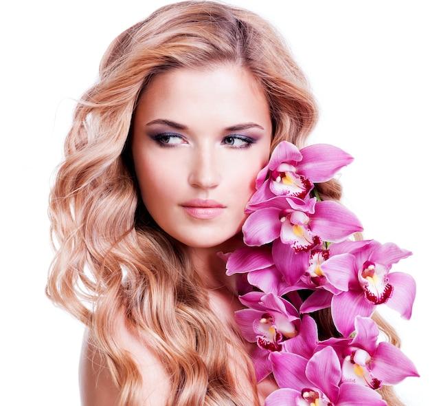 Mooi gezicht van jonge blonde vrouw met gezonde haren en roze bloemen in de buurt van gezicht - geïsoleerd op wit. Gratis Foto