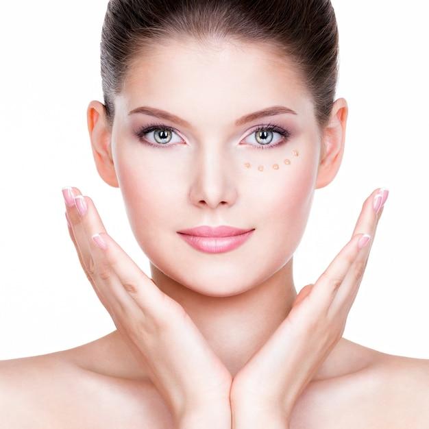 Mooi gezicht van jonge vrouw met cosmetische foundation op een huid over witte muur. schoonheidsbehandeling concept. Gratis Foto