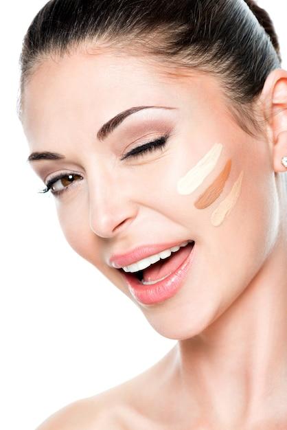 Mooi gezicht van jonge vrouw met cosmetische foundation op een huid. schoonheidsbehandeling concept Gratis Foto