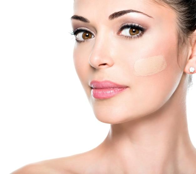 Mooi gezicht van jonge vrouw met cosmetische foundation op een huid. Gratis Foto
