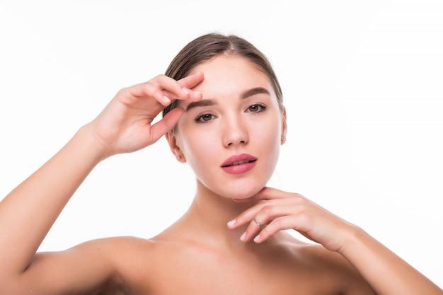 Mooi gezicht van jonge vrouw met schone huid geïsoleerd op een witte muur Gratis Foto