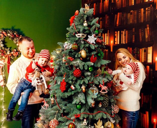 Mooi gezin met kinderen in warme truien vormt voor een groene muur en een rijke kerstboom Gratis Foto