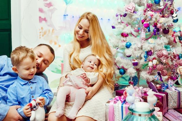 Mooi gezin met kinderen in warme truien vormt voor een muur en een rijke kerstboom Gratis Foto