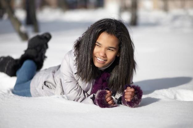 Mooi glimlachend amerikaans zwart wijfje dat in sneeuw in openlucht ligt Gratis Foto
