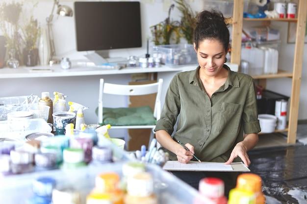 Mooi glimlachend jong wijfje dat op school van kunsten bestudeert die aan huistaak werkt, die bij moderne ruime workshop zit, tekeningen met potlood maakt Gratis Foto