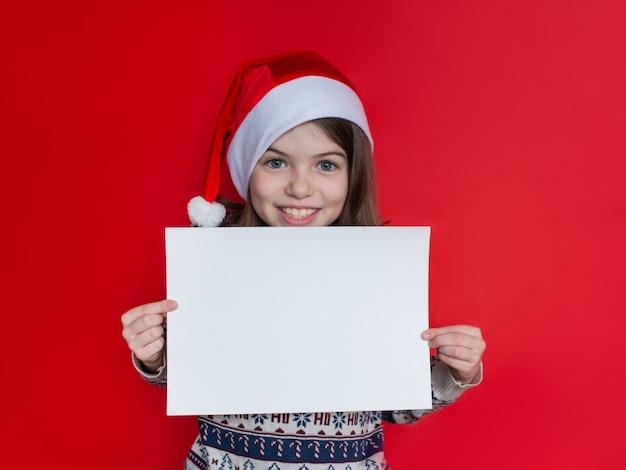 Mooi glimlachend meisje in een reclameconcept van de kerstmanhoed voor het nieuwe jaar en kerstmis Premium Foto