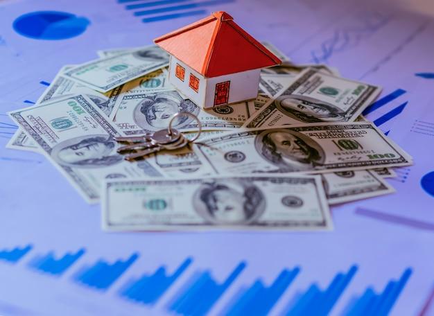 Mooi huis dat zich op 100 dollarsrekeningen bevindt. huiskosten of investeringsconcept. Premium Foto