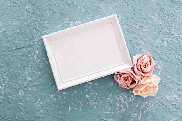 Mooi huwelijkskader met rozen op blauwe geweven achtergrond Gratis Foto