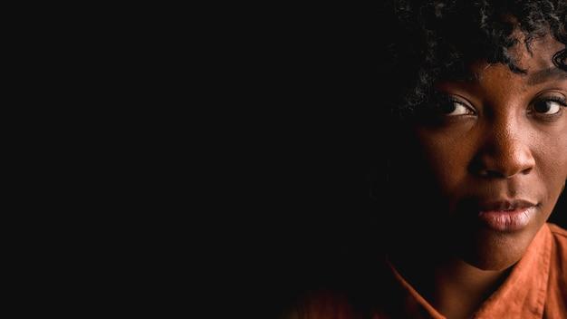 Mooi jong afro donkerbruin wijfje op zwarte achtergrond Premium Foto