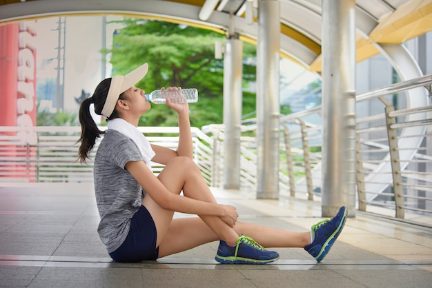 Mooi jong azië vrouwen drinkwater na opleiding. Premium Foto