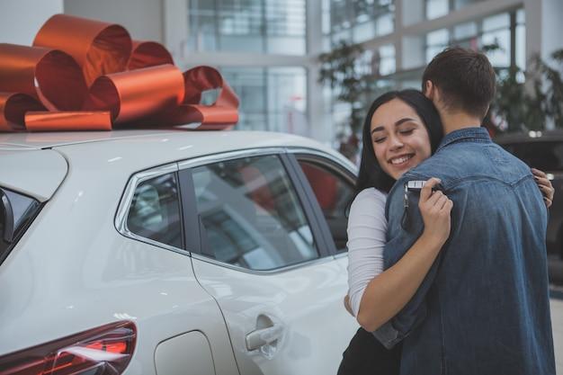 Mooi jong echtpaar dat nieuwe auto samen koopt Premium Foto