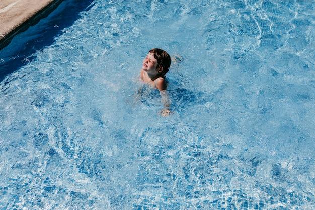 Mooi jong geitjemeisje bij het zwembad dat en pret zwemt heeft. plezier buitenshuis. zomer en levensstijl concept Premium Foto