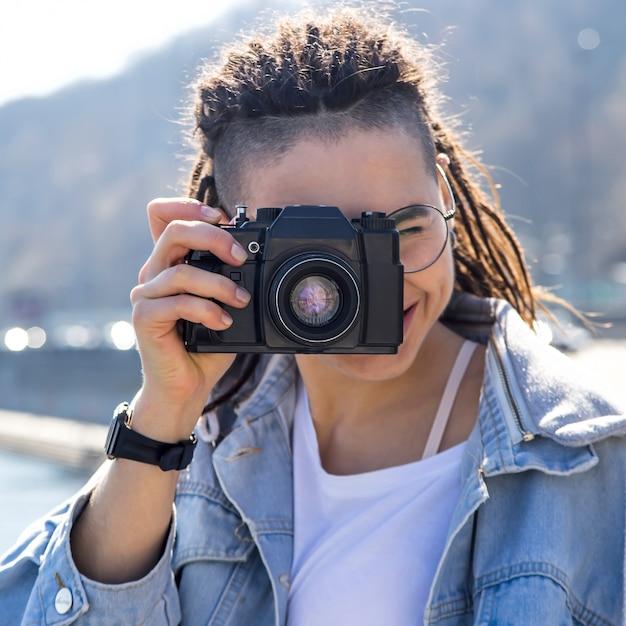 Mooi jong kaukasisch meisje met dreadlocks die een retro camera in haar handen houden - fotografie als hobby in het reizen Premium Foto