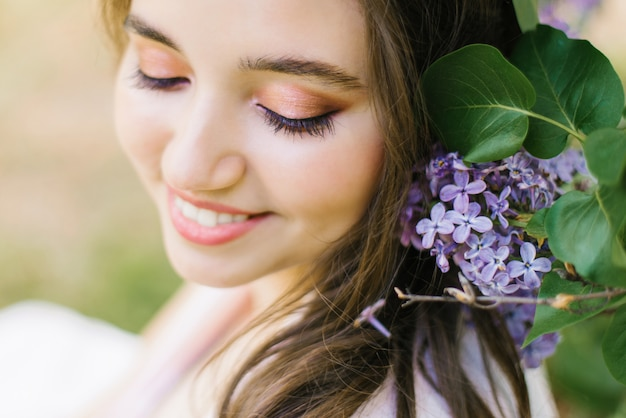 Mooi jong leuk meisje met professionele make-up dichte omhooggaande en verblindende witte glimlach met lila gelukkige bloemen Premium Foto
