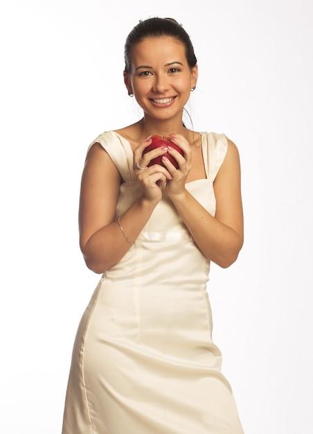 Mooi jong meisje dat u een gezond uitziende rode appel overhandigt. geïsoleerd op wit. Premium Foto