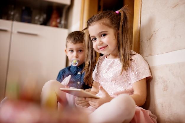 Mooi jong meisje en haar broertje, tablet spelletjes spelen in de vloer. Premium Foto