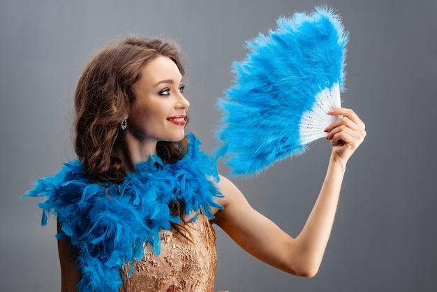 Mooi jong meisje in een blauwe boa die een ventilator van veren in zijn hand houdt Premium Foto