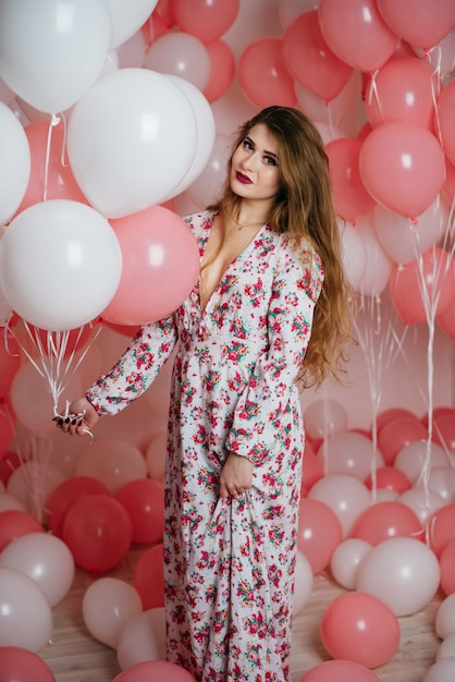 Mooi jong meisje in een jurk onder veel roze ballen. Premium Foto