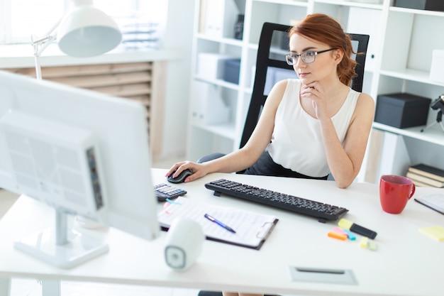 Mooi jong meisje in het bureau dat bij de computer werkt. Premium Foto