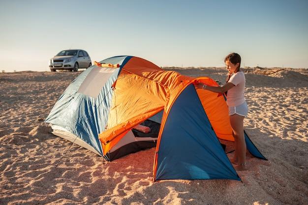 Mooi jong meisje met donker haar zet een tent op het strand Premium Foto
